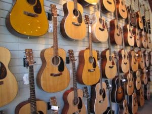 Acoustic Guitars - a collection of guitars hanging on a wall